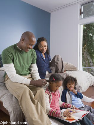 Picture of a typical African American family at home having family time, reading and happy and smiling.The kids are sitting on the hardwood floor and the parents are sitting above them on the bed.