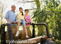 Travel and vacation picture of a family in a jeep going 4 wheeling off-road.  Travel off-road vacation family picture.  Pictures of an off-road vacation for the family album.  Happy smiling people in their jeep.