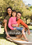 Picture of a Hispanic family on an outing to the park and the wading pool. Mother father and daughter have their bare feet in a wading pool as they pose for this hispanic family photo.  Happy smiling people pictures for ads.