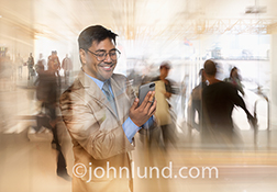 Fast connections on the go, whether personal, business or social, are illustrated in this stock photo of a businessman using his touch screen phone in a busy retail environment.