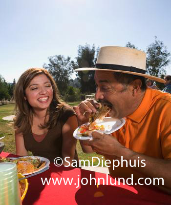 Picture Of A Mexican Family Eating Food At Picnic In The Park