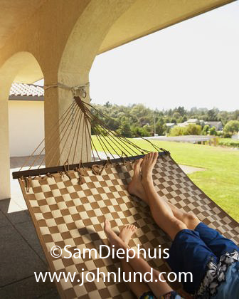 View of the legs and bare feet of a father and his son who are relaxing on a large hammock strung between columns.