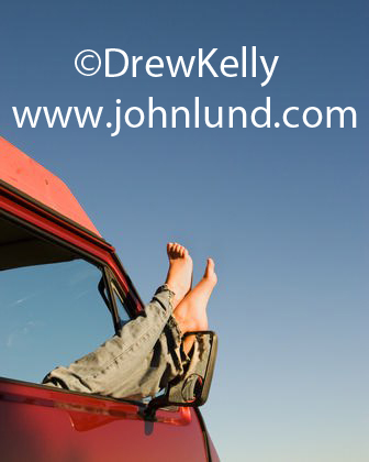 Stock photo of a womans legs and feet sticking out from the window of a van. The woman's legs are crossed and she is wearing long pants.  Bare feet out car window.