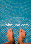 Photo looking straight down of a mans feet under water in a swimming pool, spa, or wading pool with tiled bottom.  A round ripple is showing in the water right at the toes on his left foot.