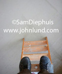 Picture of a mans feet standing on the top of a wooden step ladder. The camera is looking straight down at the pair of work shoes worn by the man on the ladder.  Business and advertising photogrpahy.