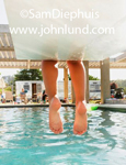 A young childs feet are hanging over the water as the kid sits on the end of a diving board at a public swimming pool. Picture taken from under the diving board.