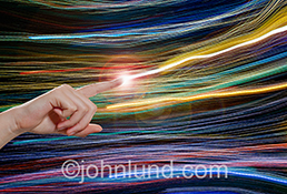 A bright streak of light shoots out of a finger against a background of vividly colored light trails in a stock photo about communications, connection, technology and the future.