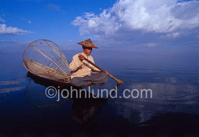 Picture of a Burmese fisherman on beautiful scenic Inle Lake. Background stock photos. A man rows his dugout boat across Inle lake.  Behind him is his conical fishing net, the kind the fishermen of Inle Lake are famous for.