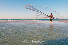 A fisherman tosses out his net on the Yemeni island of Socotra in an adventure travel image showcasing one of the many pristine white sand beaches that ring the island.