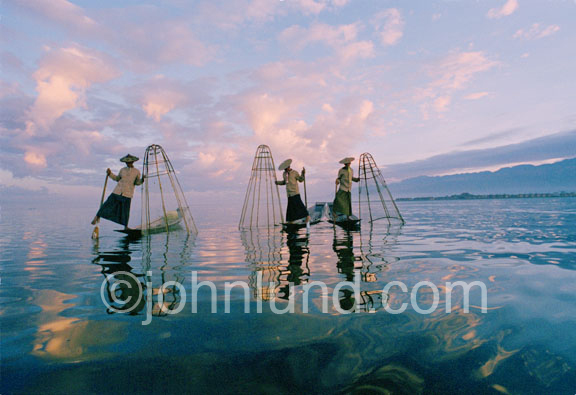 Travel and adventure picture of three fishermen fishing in a lake in Burma. They steer and propel their boats (dugout canoes) with a paddle held with one hand and powered by one leg and foot.
