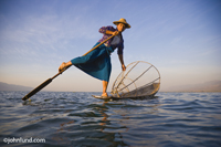 A Fisherman is Rowing his boat with his leg on Inle Lake, Myanmar at sunset. A conical fishing net is on his boat.