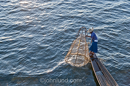 High view of a Burmese fisherman on Inle Lake, Myanmar, using a conical net in the late afternoon.