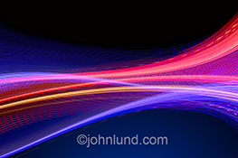 Big data, streaming data, and communications technology are illustrated in this stock photo of vividly colored light trails elegantly flowing across the frame. Additional concepts include bandwidth, speed and wireless technology.