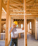 Picture of  a Foreman or Supervisor on the job site using his cell phone and holding blue prints in his hand. The foreman is standing amid naked framing without walls or ceiling. Advertising pictures of new construction and contractors at work.