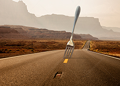 A giant fork protrudes from a long empty road,  a humorous take on the idea of a