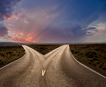 A fork in the road diverges with one road leading to a sunrise and the other to a cloudy sky in a stock photo about choice and decisions.