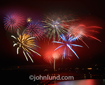 A beautiful fourth of July fireworks display over San Francisco Bay is the subject of this photo highlighting the excitement and vibrant color of the celebratory explosions reflected in the bay waters.