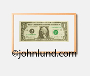 Picture of  framed dollar bill, as in the first dollar made or the first dollar earned by an small business or business owner.  Wood colored frame around a one dollar bill on a white background with George Washingtons face showing.