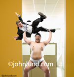 Funny picture of a Sumo wrestler in an office. Sumo wrestler holding a businessman over his head about to throw him away. Funny office photo. Conceptual pictures of sumo wrestlers in an office environment.