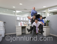 Funny picture of four business people riding piggyback on another businessman in an office setting.
