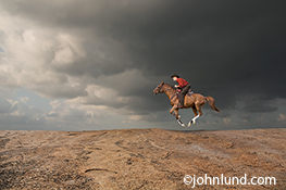 An equestrian gallops his horse across a rocky ridge under the threatiening clouds of a thunderstorm in an image about speed, the way forward, skill and courage.