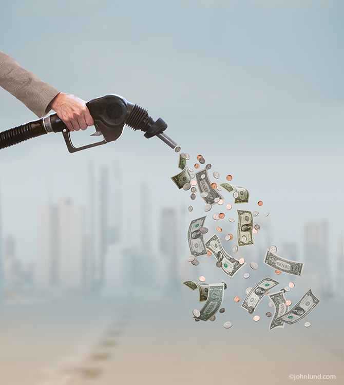 A person's hand holds a gas pump nozzle out of which are flowing currency and coins that cascade down out of the frame in an image about issues surrounding the costs of fuel, the price of gas, and conservation.