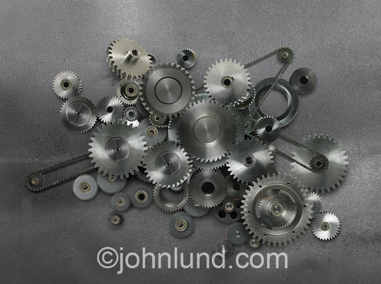 A combinations of gears (cogs) and chains form a complex configuration in a visual metaphor for working, complexity and even relationships.
