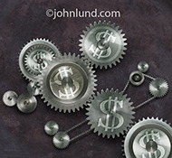 An assembly of gears in which dollar signs are embossed on the gear surfaces is the subject of this photographic metaphor for the interplay of money, infrastructure and the working environment. This image illustrates the old saying that money makes the wo