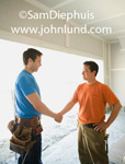Carpenters shaking hands on the job.  Two construction site workers are standing in an unfinished building and are shaking hands. Picture of working men shaking hands on the job for advertising and advertisments.