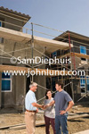 General contractor shaking hands with happy new homeowner couple. The three people are standing in front of a new home under construction surrounded by scaffolding. Completing the deal.