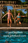 Picture of two young girls holding hands as they jump into the blue swimming pool. One girl is wearing a striped one piece swimsuit and the other young girl is wearing a blue two piece suit.  Kids having fun in the swimming pool pics.