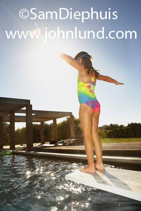A young female child standing on the end of a diving board preparing to dive into a swimming pool. She has a colorful bathing suit on and she has her arms stretched out at her sides.