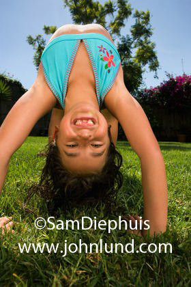 Cute young hispanic girl playing in the grass. She is doing summersalts and hand stands. She is smiling at the camera with big smile that is missing some front teeth.  Pics of young girls with missing front teeth.
