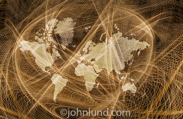 A global networking map is seen in this stock photo in the form of an intricate and complex light trail network multiple exposed with a map of the world's continents.