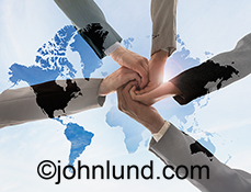 Global teamwork is represented in this stock photo of four hands coming together over a map of the continents showing cooperation and success.