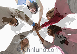 Global teamwork is cleverly illustrated in this stock photo of an ethnically diverse group of five people joining hands superimposed over a global map of earth's continents.