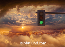 In a beautiful high altitude cloudscape at sunset a green stoplight indicates it is all
