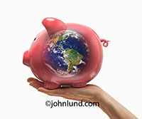 A hand holds up a piggy bank in which the earth can be seen within in an image representing green investment, world finance, and the Global Economy.