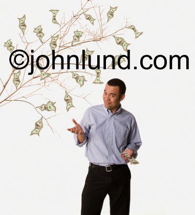An ethnic business man poses next to a money tree with dollar bills that look like leaves on the branches of the money tree. The man has on dark slacks and a blue dress shirt with no tie.