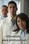 Picture of a group of doctors in their white lab coats. Two male doctors and a female doctor standing together for a portrait.  Medical pictures of doctors for advertising.