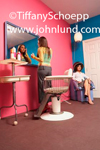 Photo of a woman in a beauty parlor putting on makeup or checking her makeup  in front of a mirror on the wall.  Another woman sits under a hair dryer in the corner.  Wall is pink. Beauty parlor pic.