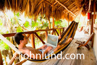 Bare chested man relaxing in a hammock under a thatched roof and using his laptop deep in the jungles of Mexico.