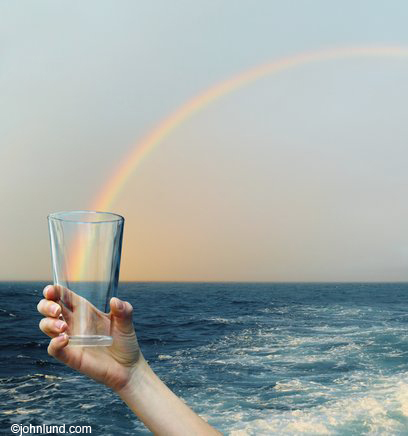 A glass is held up so that it appears to capture a rainbow over the ocean in stock photo about hope and possibilities.