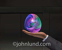 In this future technology stock photo a businessman's hand holds an orb of vividly colored light trails in an image about the future, energy, communications and technology.