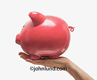 This image of a hand holding a piggy bank represents persona finance, savings, and investment in a versatile, quick reading and clear message.