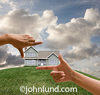 A pair of hands are seen framing a house on a hill, envisioning a dream house and imagining greeat things to come in a concept image about possibilities and success.