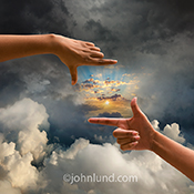 A pair of hands frame a sunrise appearing through overcast skies and thick clouds in a stock photo about better times ahead, opportunity, and success.