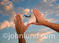 Stock photo of a pair of hands being held up to the cloudy sky framing a passenger jet flying through the air. Mans hands. Travel stock photos.