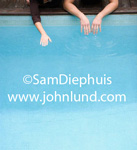 Picture of the edge of a swimming pool with some kids hands reaching into the water to feel the temperature perhaps.  One pair of hands in the water and a third hand also in the blue water.
