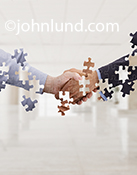 The hands of two business people com together in a hand shake in which jigsaw puzzle pieces are out of place in a metaphor for business negotiations, relationships and connections.